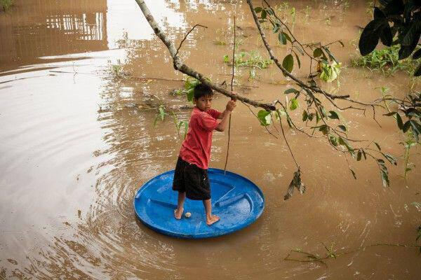 A young boy plays in the Amazon river.